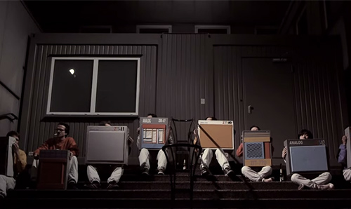 Film still from 'Krach Kisten Orchester Leca Platte' featuring musicians sitting on steps holding speakers.