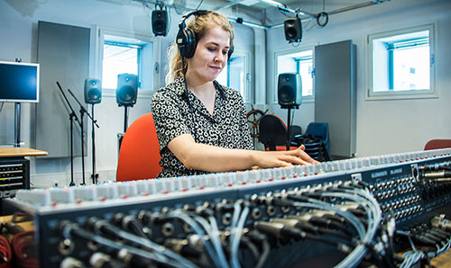 Female student with headphones at the mixing desk in Studio One